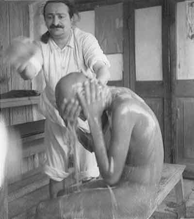 Meher Baba washing a mast 1946